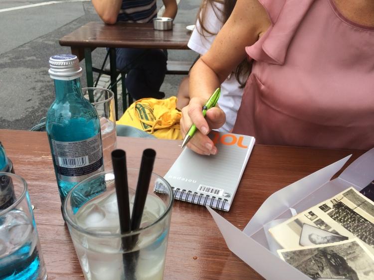 Hånd, penn, blokk og cafebord