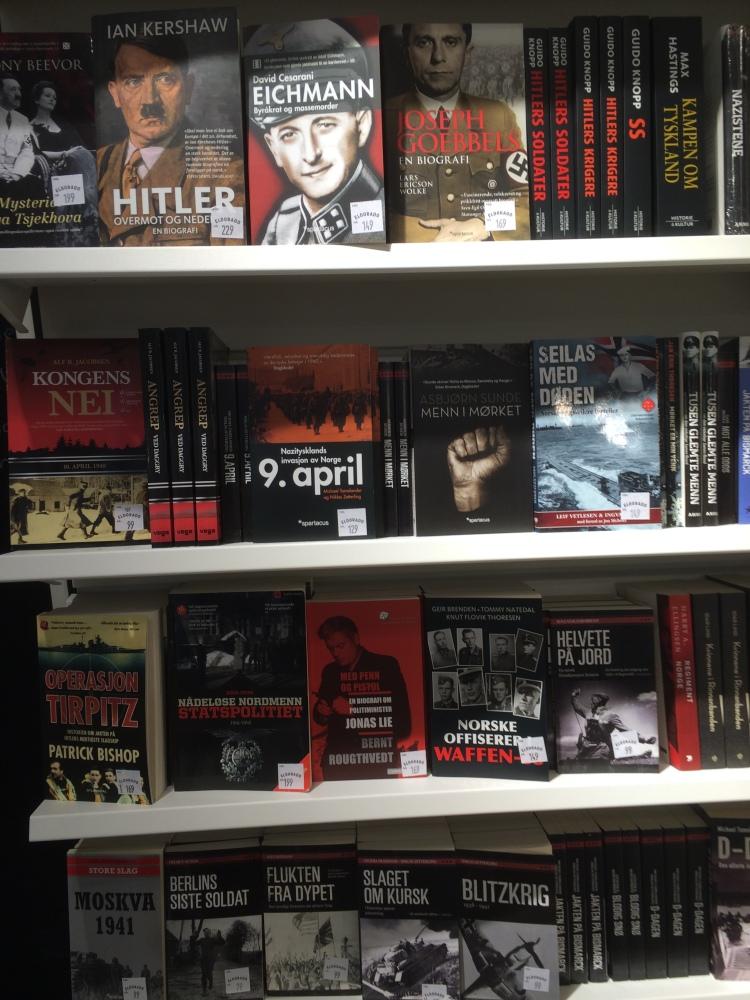 En bokylle med masse sorte og røde bøker med dystre bilder og knyttede never med titler som Hitler, Eichmann og 9. april. Doom and gloom.