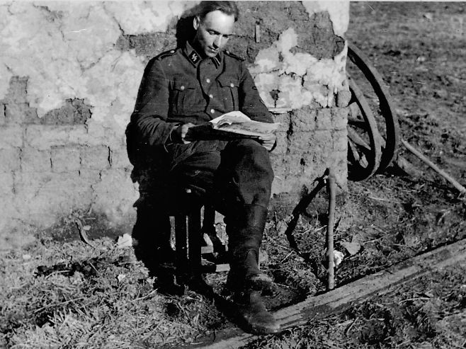 Sort hvitt bilde av en ung mann i SS-uniform som leser en avis i solveggen